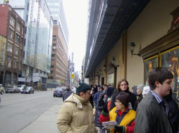 People standing outside of The Canon Theatre (Ed Mirvish Theatre) in Toronto hoping to win lottery tickets to Rent.